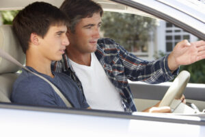 Father teaching teenager how to drive